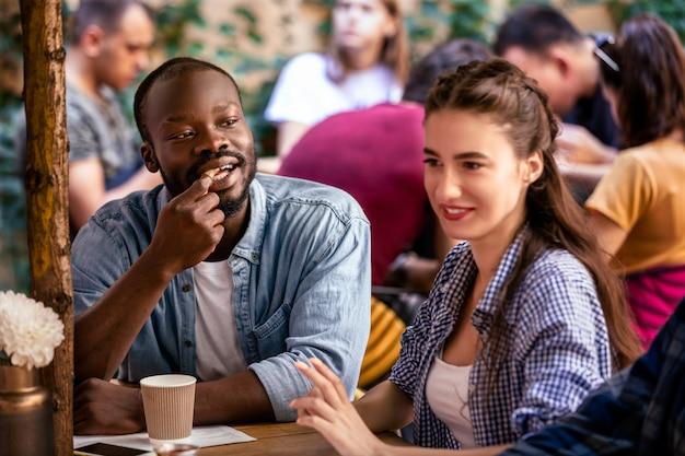 Casal multicultural tem uma data em um restaurante aconchegante local em um dia quente e ensolarado