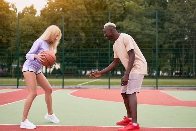Casal multiétnico ativo jogando basquete em uma quadra de esportes ao ar livre. um negro ensinando sua namorada loira a jogar streetball