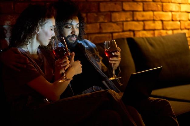 Casal multiétnico bebendo vinho tinto enquanto assiste a filmes, filmes, comédias. mulher bonita adora passar o tempo com o namorado em casa