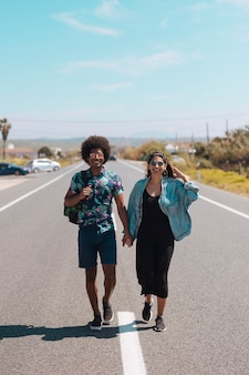 Casal multiétnico caminhando na estrada