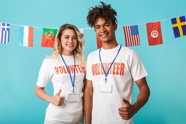 Casal multiétnico e confiante e feliz, vestindo uma camiseta de voluntário isolado na parede azul