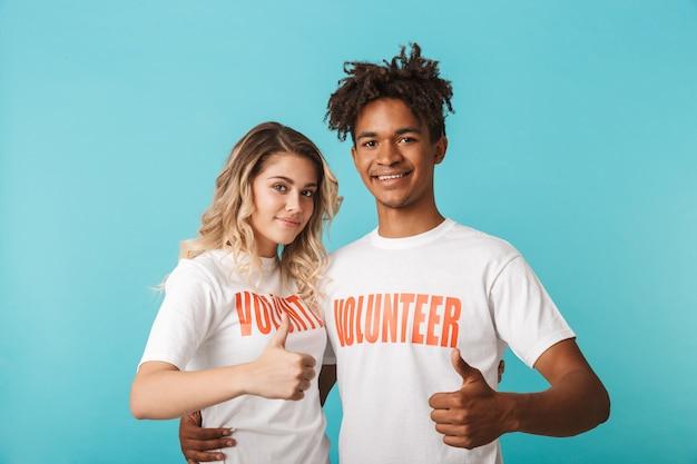 Casal multiétnico e confiante feliz vestindo camiseta de voluntários em pé, isolado na parede azul, polegar para cima