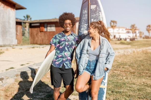 Casal multiétnico em pé com pranchas de surf