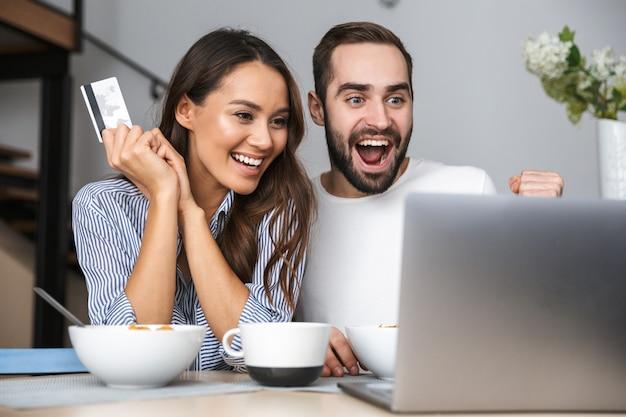 Casal multiétnico feliz tomando café da manhã na cozinha, olhando para o laptop, mostrando o cartão de crédito