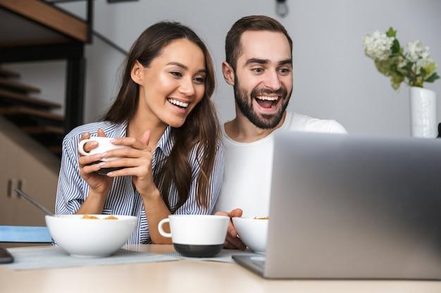 Casal multiétnico feliz tomando café da manhã na cozinha, olhando para o laptop