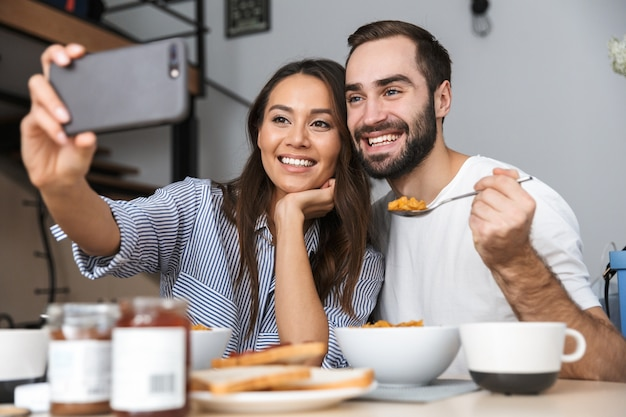 Casal multiétnico feliz tomando café da manhã na cozinha, tirando uma selfie