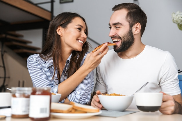 Casal multiétnico feliz tomando café da manhã na cozinha
