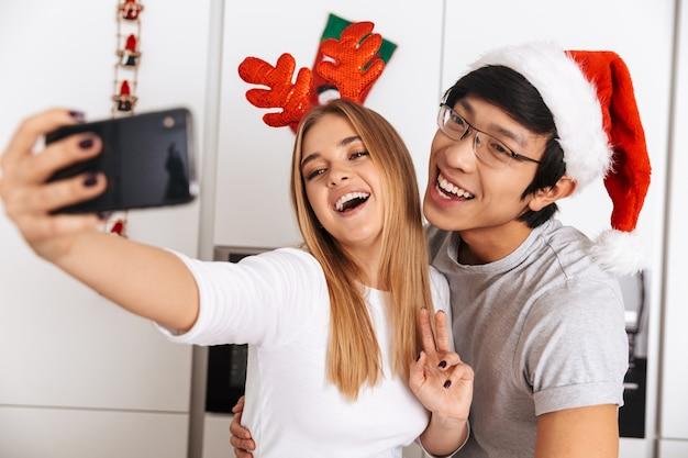 Casal multiétnico, homem e mulher vestindo roupas de natal, em pé na cozinha bem iluminada e tirando foto de selfie no celular