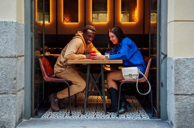 Casal multiétnico olhando para um smartphone em um restaurante