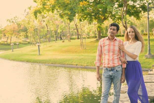 Casal multiétnico pensando em pé em um caminho de pedra no meio do lago em um parque verde tranquilo