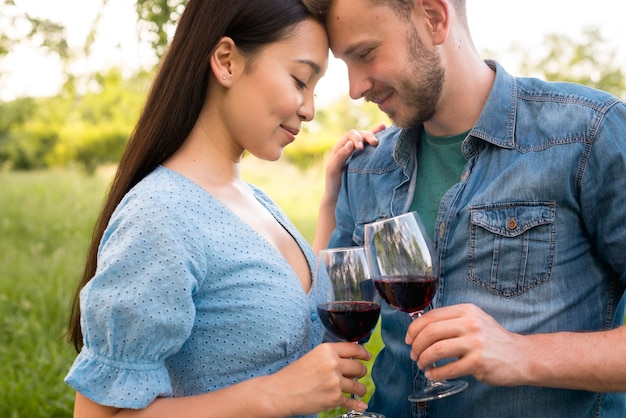 Casal multiétnico romântico segurando copos de vinho