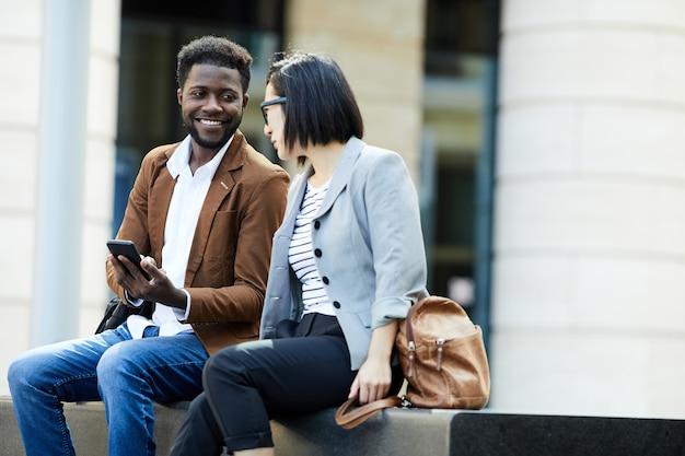 Casal multiétnico usando smartphopne ao ar livre