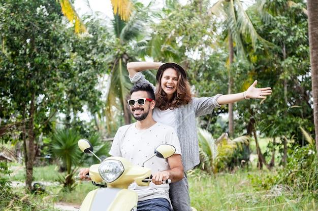 Casal multinacional feliz viajando de moto na selva, lua de mel, férias,