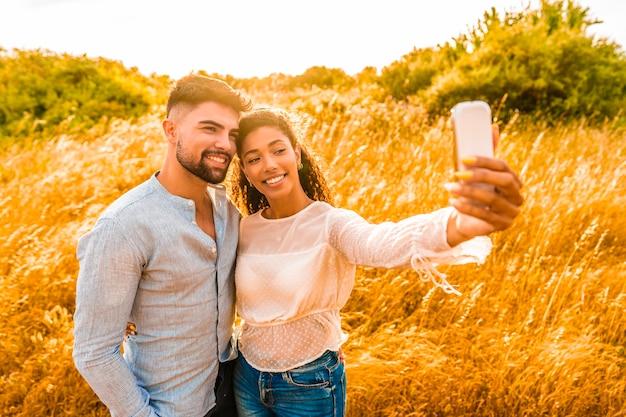 Casal multirracial apaixonado se divertindo com smartphone tomando selfie na natureza. garota hispânica se fotografando com o namorado ao pôr do sol para compartilhar as férias nas redes sociais. jovens bonitos