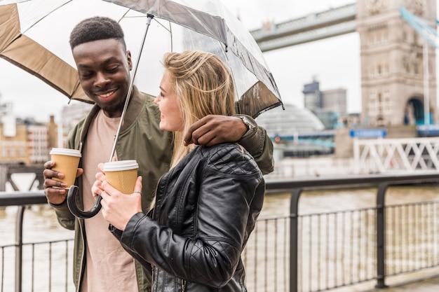 Casal multirracial feliz andando em londres segurando um guarda-chuva