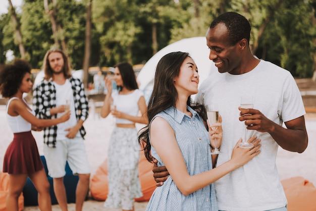 Casal multirracial romântico bebendo champanhe