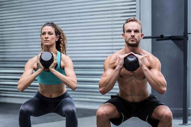 Casal muscular exercitando com kettlebells