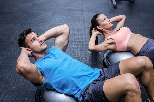 Casal muscular fazendo choque abdominal