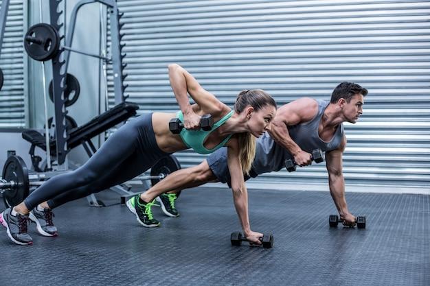 Casal muscular fazendo exercício de prancha em conjunto