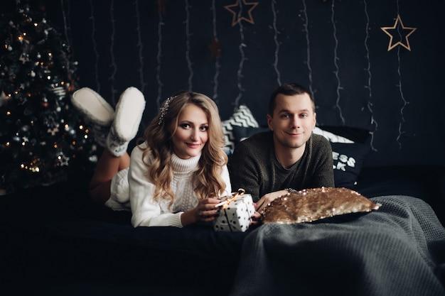Casal na cama com presente de natal ano novo