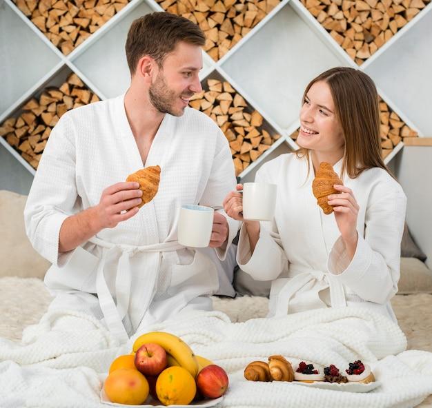 Casal na cama com roupões de banho e frutas