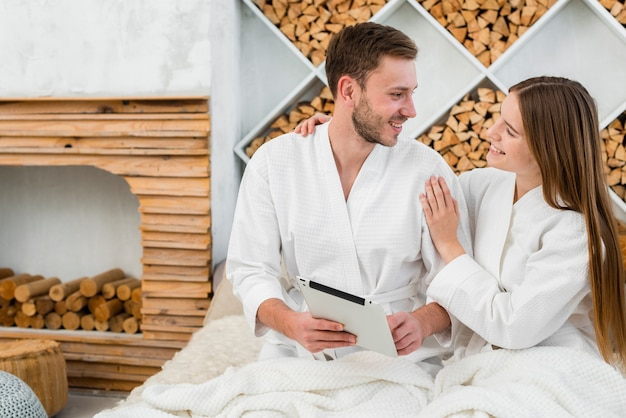 Casal na cama com tablet e roupões de banho