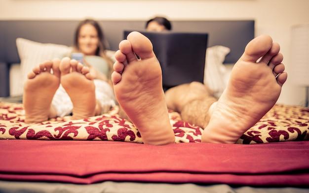 Casal na cama e tecnologia