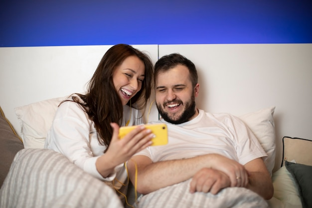 Casal na cama olhando para smartphone