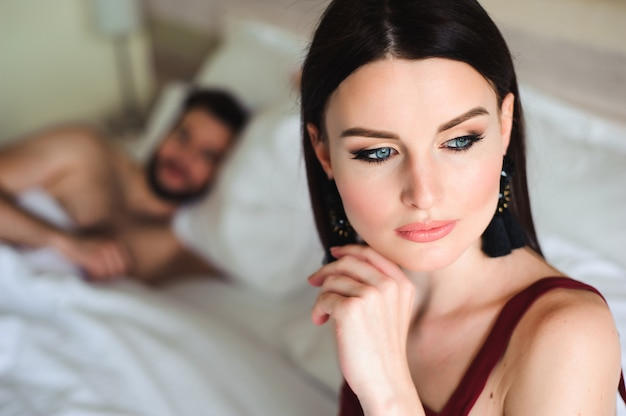 Casal na cama, retrato de uma mulher triste na cama com o marido