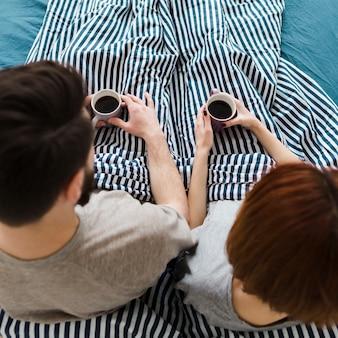 Casal na cama segurando xícaras de café