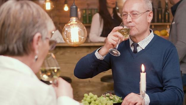 Casal na casa dos 60 anos bebendo vinho enquanto estão em um restaurante para almoçar. casal romantico. casal de idosos.
