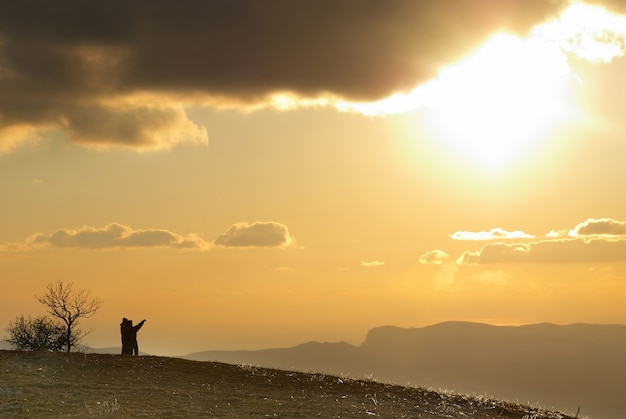 Casal na colina contra o pôr do sol com nuvens e céu