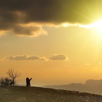 Casal na colina contra o pôr do sol. paisagem com nuvens e céu.