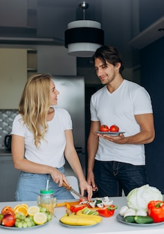 Casal na cozinha em pé com comida saudável e olhando uns aos outros. imagem vertical