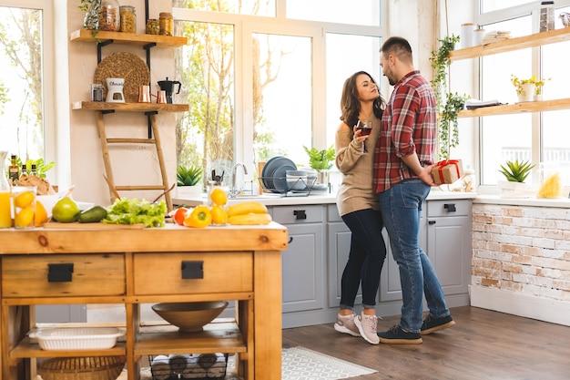 Casal na cozinha. homem de pé e segurando a caixa de presente branca nas costas.