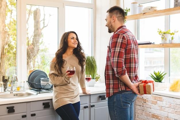 Casal na cozinha. homem de pé e segurando a caixa de presente nas costas.