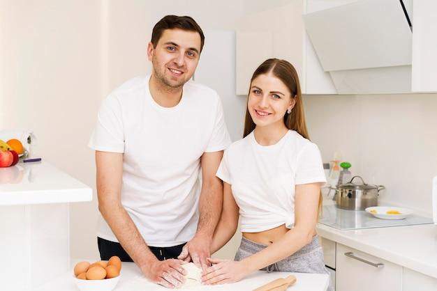 Casal na cozinha preparando massa