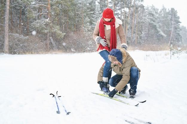 Casal na data de esqui na floresta