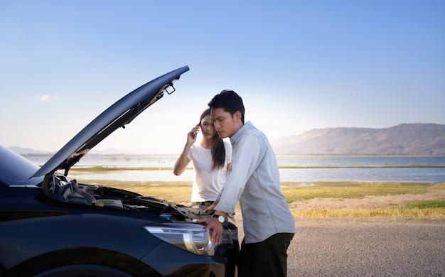 Casal na estrada tendo problema com um carro. casal após uma avaria do carro ao lado da estrada