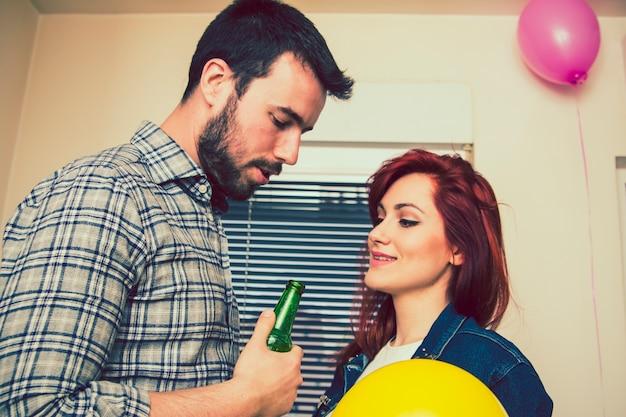 Casal na festa com cerveja e balões