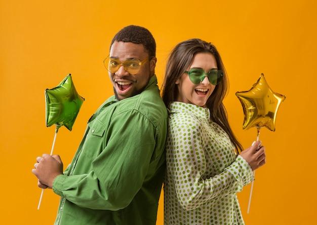 Casal na festa se divertindo e segurando balões