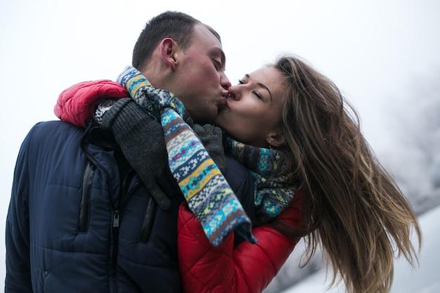 Casal na floresta de inverno perto do lago