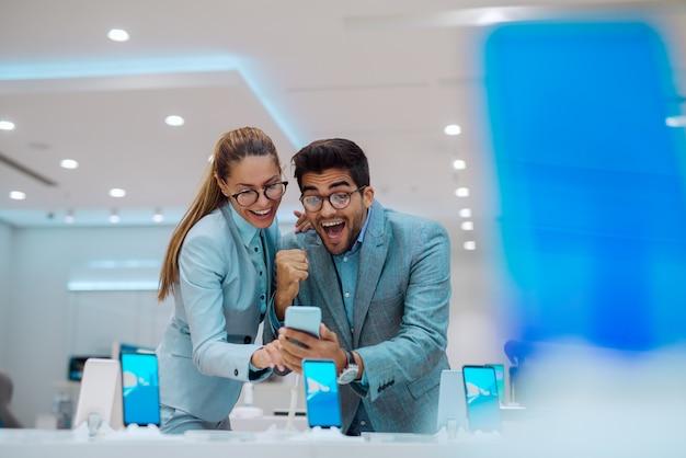 Casal na loja de tecnologia à procura de um novo telefone celular.