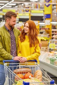 Casal na mercearia, fazer compras, escolher comida para casa juntos. prateleiras com comida. retrato