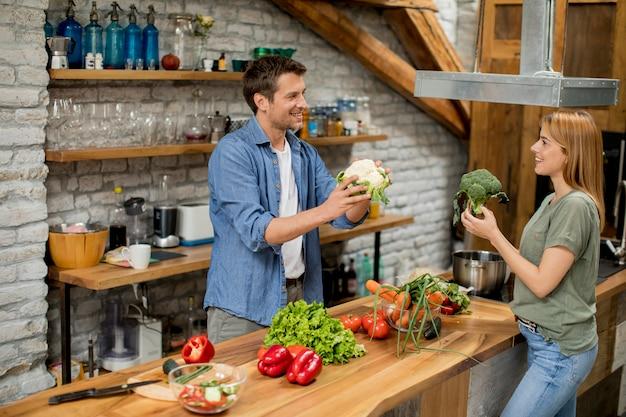 Casal na moda descascando e cortando legumes do mercado em cozinha rústica