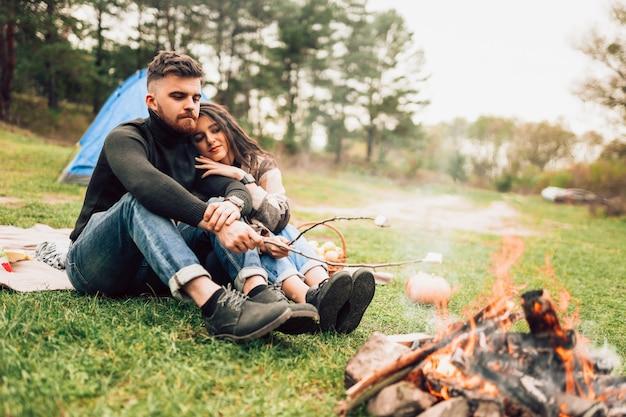 Casal na natureza assando marshmallows