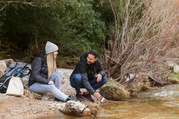 Casal na natureza bebendo água do rio