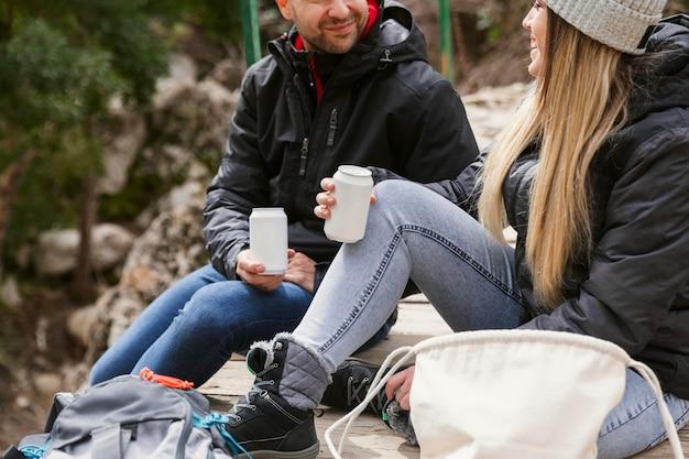 Casal na natureza bebendo água