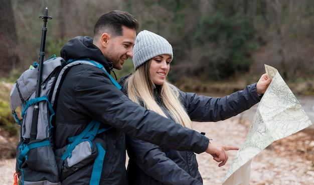 Casal na natureza consultando mapa