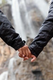 Casal na natureza de mãos dadas perto